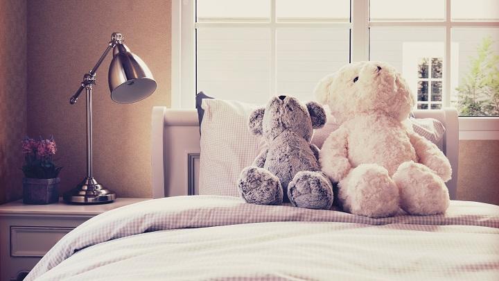 cama con peluches y una lámpara